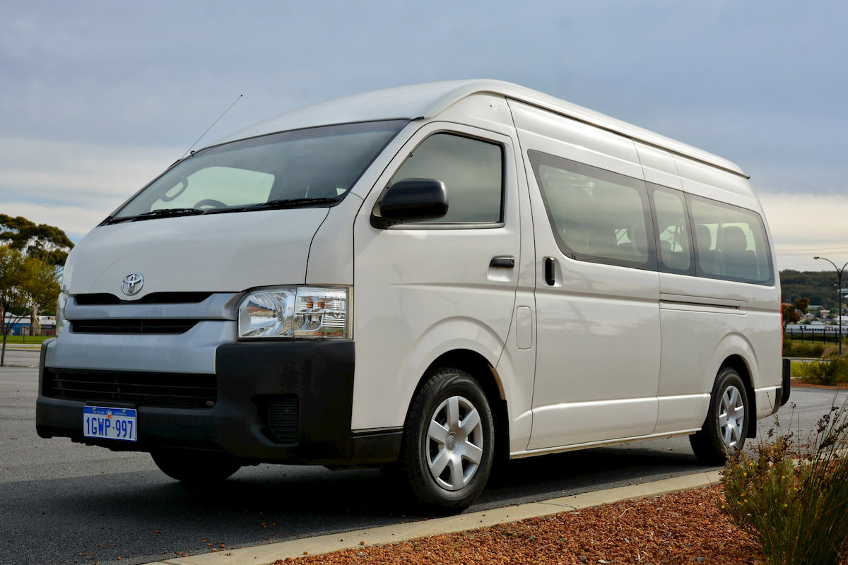 A white 12 seater Toyota Commuter bus