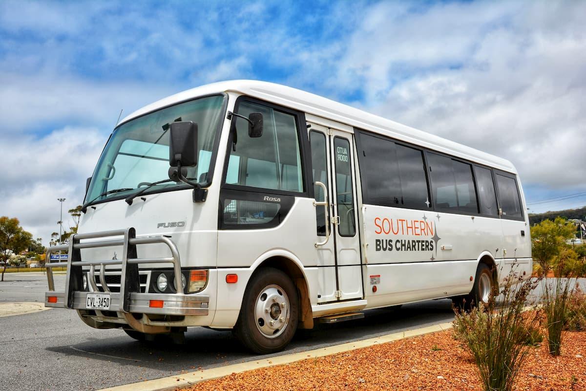 A white 21 seat Mitsubishi Rosa bus