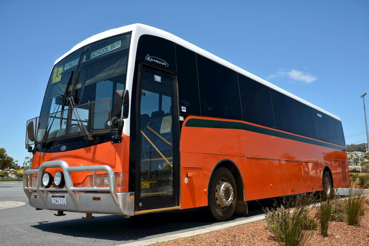 A large school bus orange 57 seat Volvo coach